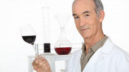 A scientist holding a wine glass in his laboratory